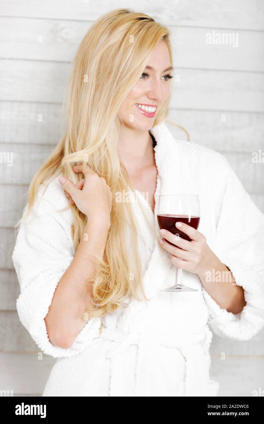 Belle jeune femme dans une robe blanche avec un verre de vin rouge Banque D'Images
