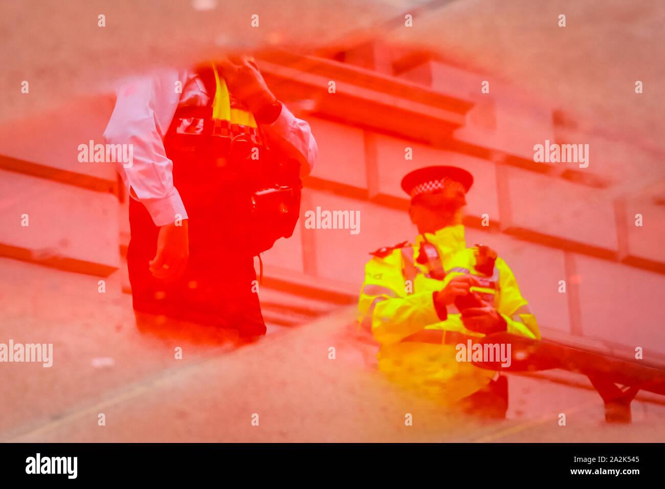 HM Treasury, Westminster, London, UK. 06Th Oct, 2019. Les agents de police sont reflétées dans une flaque de sang rouge faux extérieur HM Treasury. Rébellion Extinction manifestants ont pulvérisé l'extérieur de l'immeuble du Trésor à Westminster avec faux sang de la durit d'une friche à incendie et sont arrêtés sous forte présence policière. Credit: Imageplotter/Alamy Live News Banque D'Images