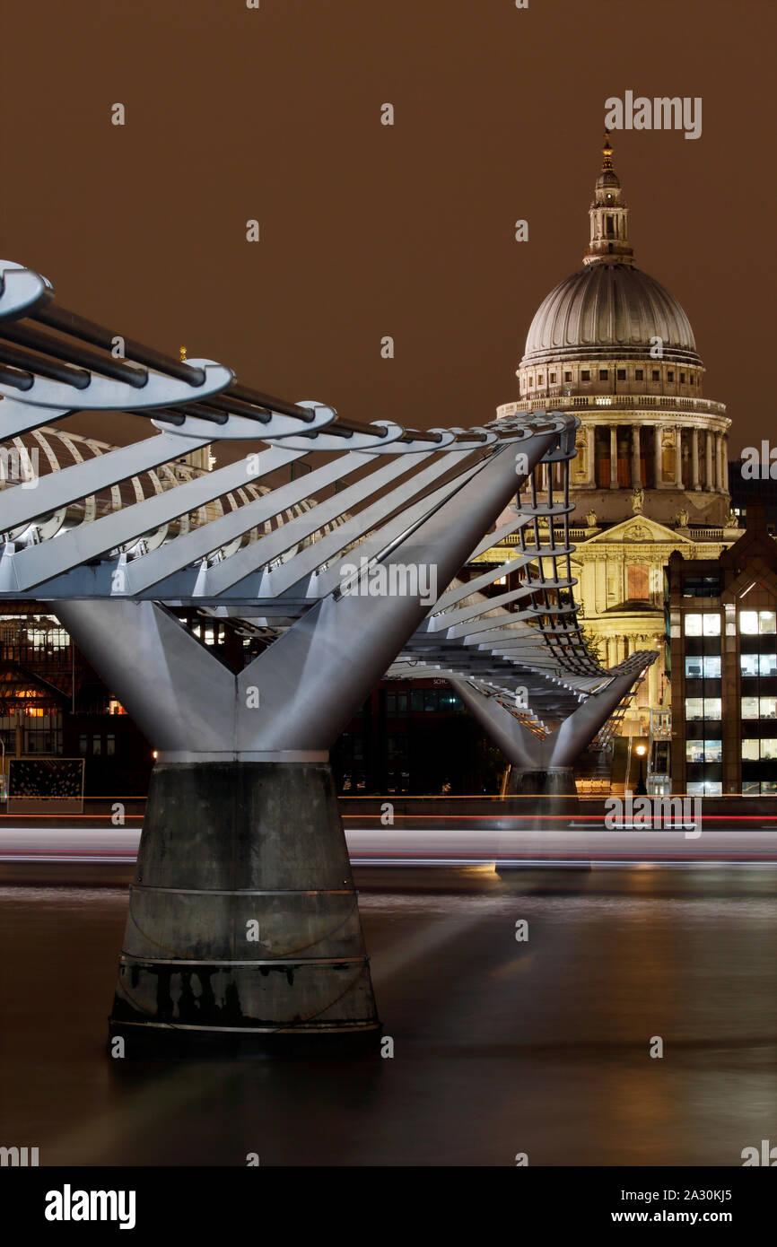 Le Millennium Bridge et de Saint Pauls Cathedral, Londres, Angleterre la nuit, avec la lumière des sentiers de bateaux de passage, une longue exposition de droit. Banque D'Images