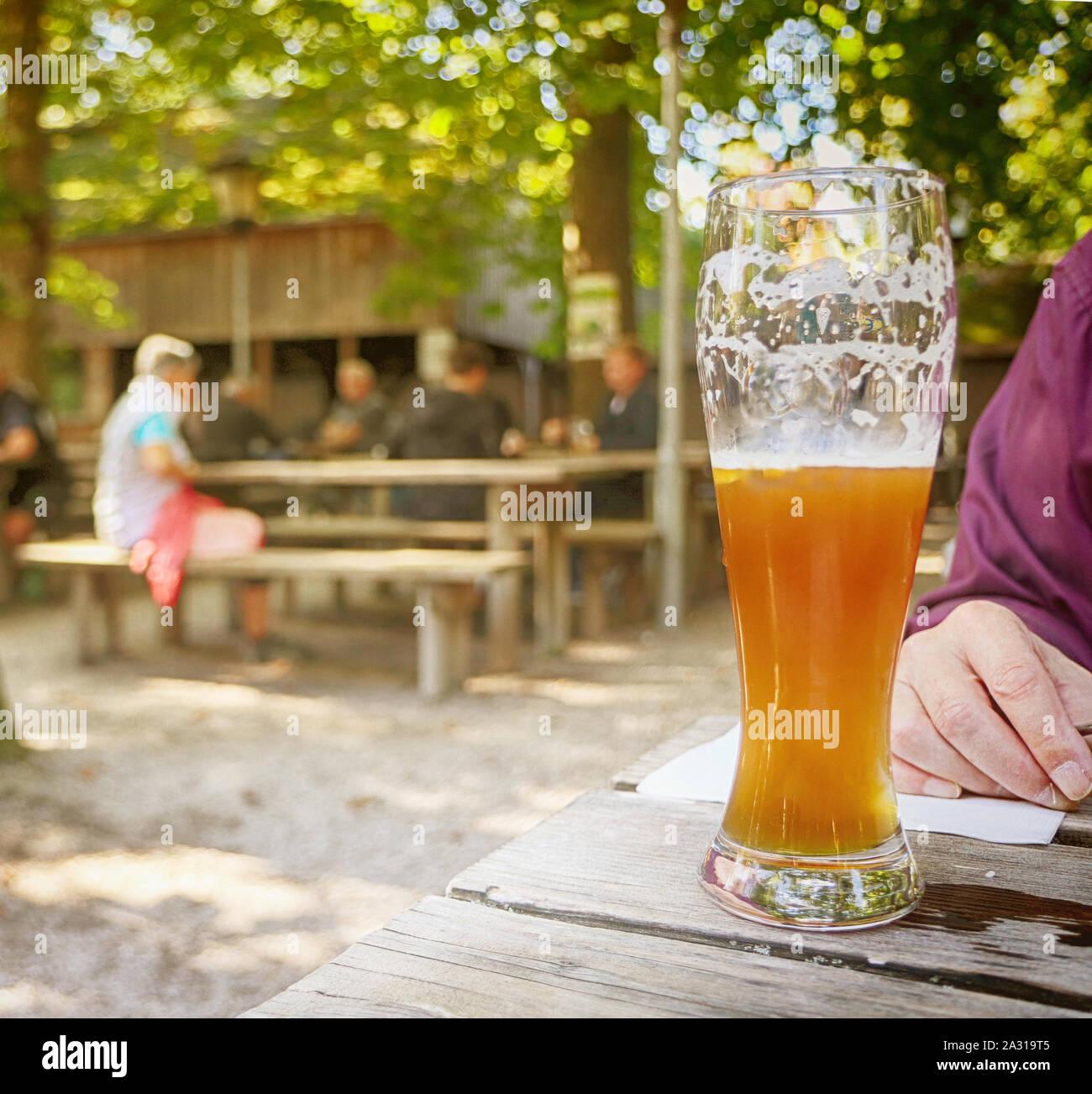 Verre de bière bavaroise au beer garden, arrière-plan flou Banque D'Images