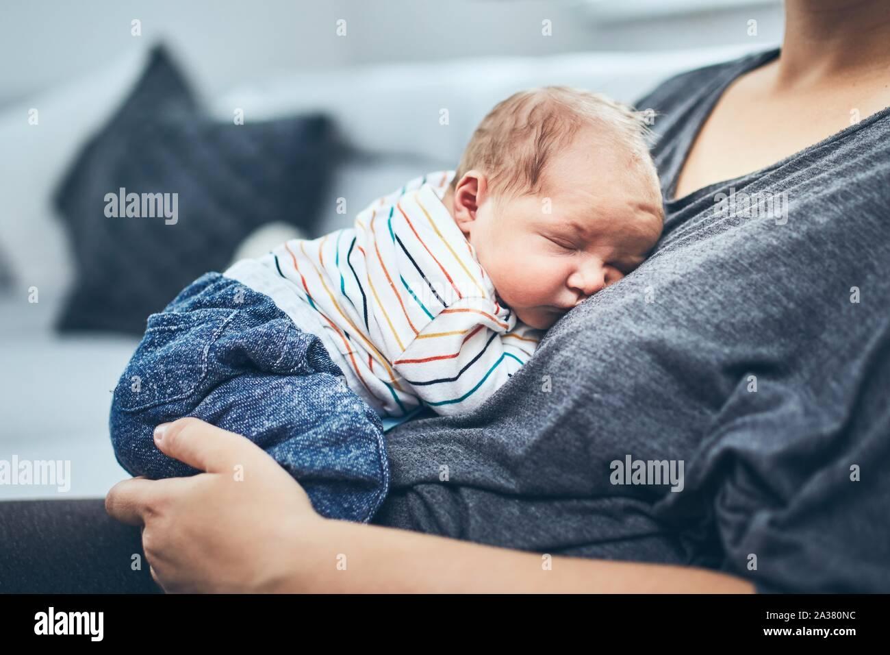 Mère avec nouveau-né. Femme tenant son fils âgé de 4 jours à la maison. Banque D'Images