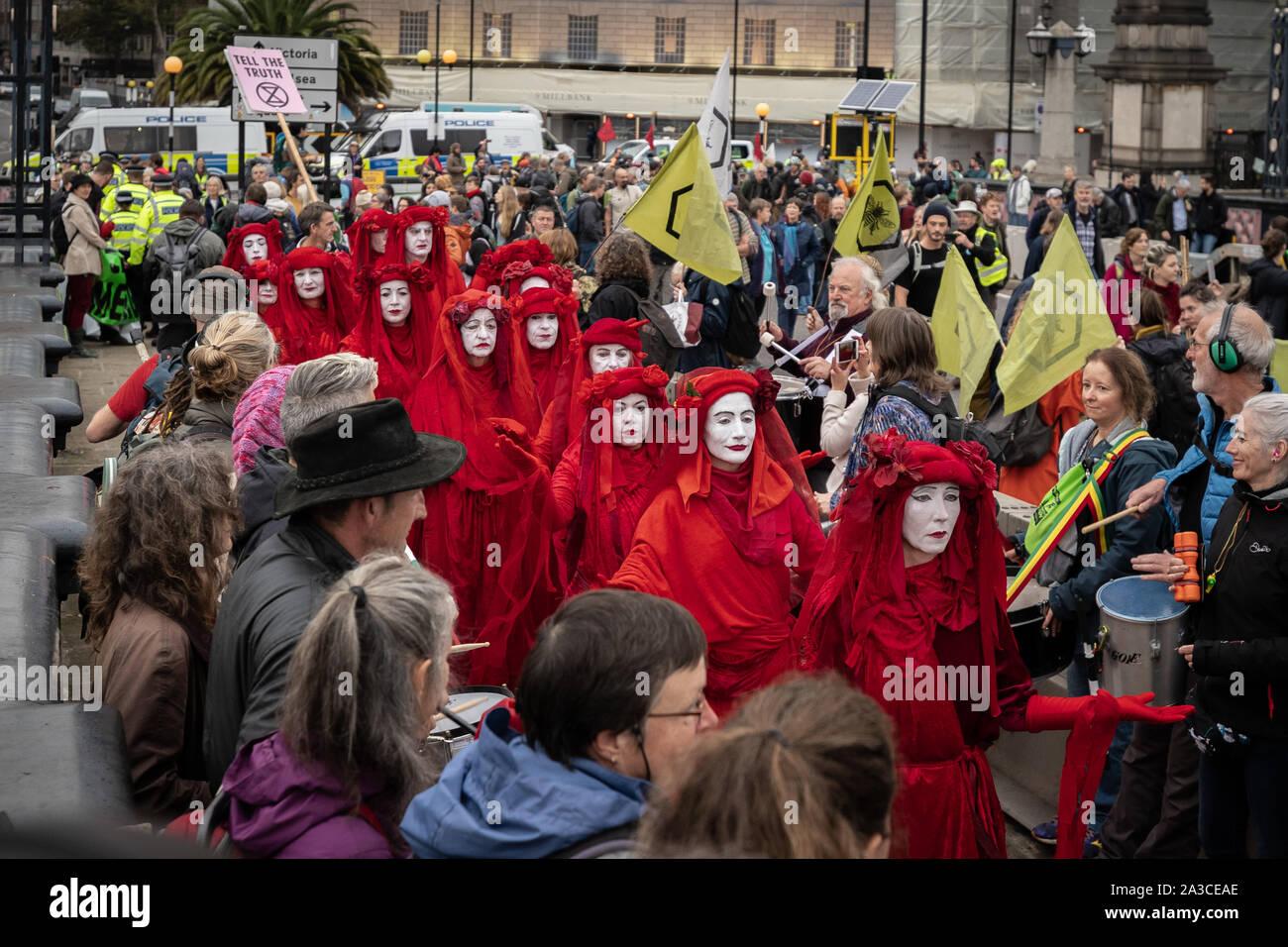 L'extinction de la rébellion rebelles rouges 'Brigade' inscrivez-vous le changement climatique militants sur Lambeth Bridge portant leur marque de vêtements rouge sang. Londres, Royaume-Uni. Banque D'Images
