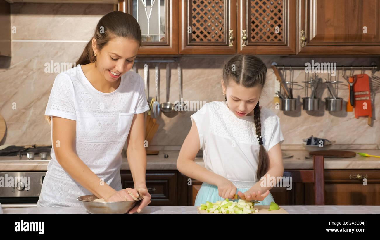 Portrait de la mère et la fille sont la cuisson tarte ensemble dans la cuisine, maman est une pâte à pétrir et sa fille ado est à la pomme. Banque D'Images