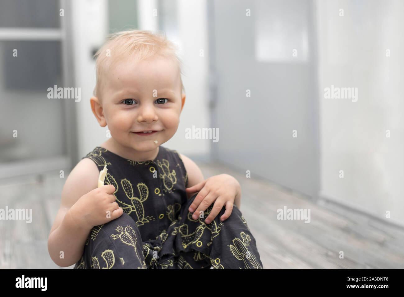 Surpris petit bébé sur le plancher à l'intérieur d'accueil Banque D'Images