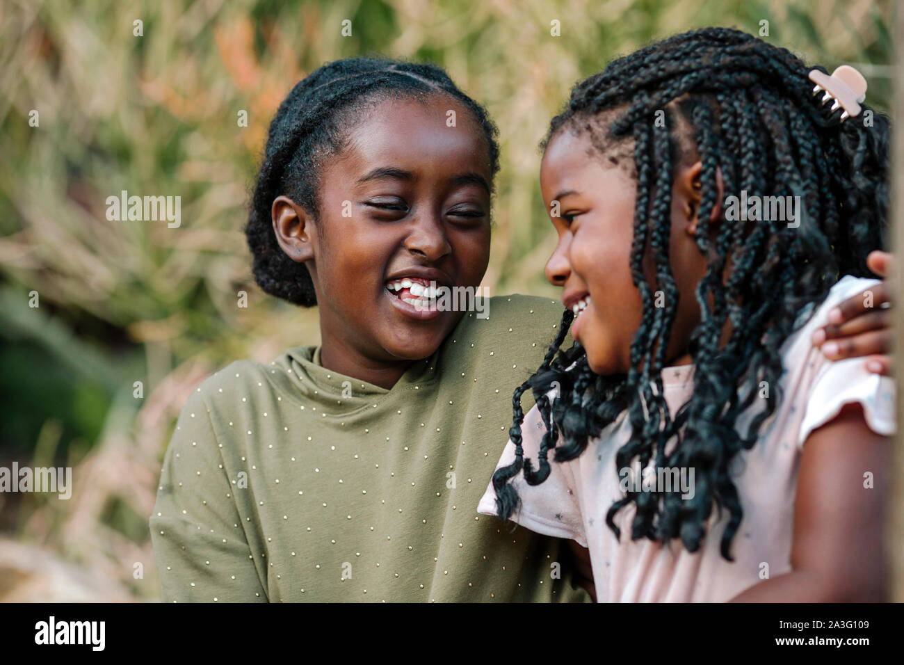 Beau rire black sisters embracing outdoors Banque D'Images