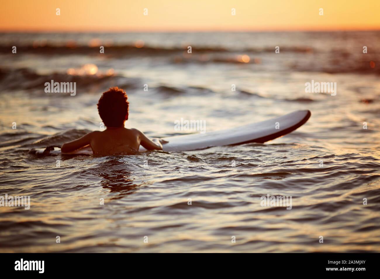 Jeune homme équitation vague au coucher du soleil. Mode de vie actif en plein air. Le surf au coucher du soleil Banque D'Images