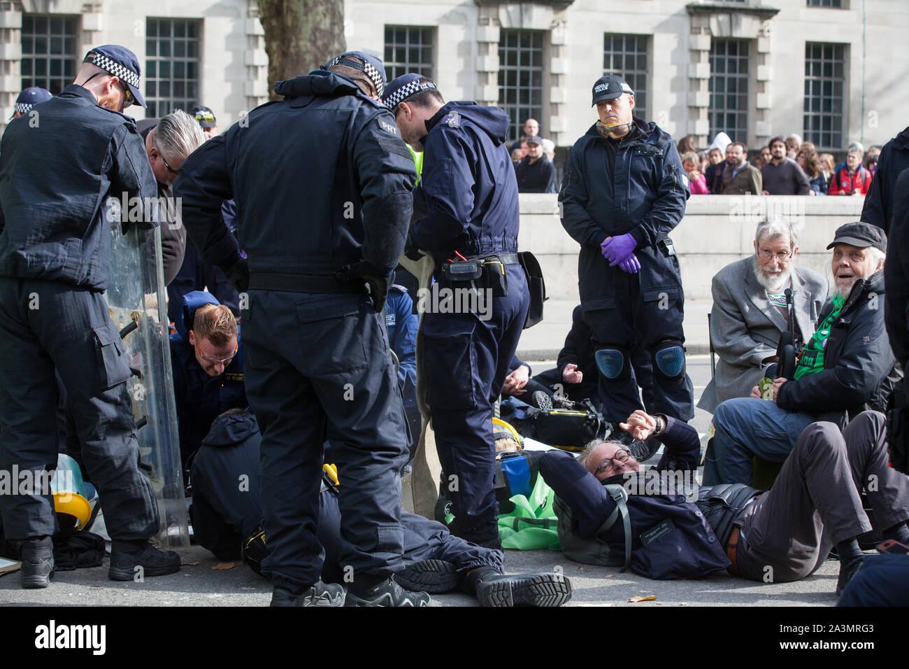Londres, Royaume-Uni. 9 octobre, 2019. John, 91 ans, et David, un grand-père, les deux activistes du climat de l'Extinction, rébellion, attendre d'être arrêté par des policiers à l'aide de l'article 14 de la Loi sur l'ordre public de 1986 après le blocage Whitehall le troisième jour de manifestations internationales d'exiger une rébellion Déclaration gouvernementale d'un climat et d'urgence écologique, un engagement à enrayer la perte de biodiversité et la consommation énergétique nette zéro émissions de carbone en 2025 et pour le gouvernement de créer et d'être entraîné par les décisions d'une assemblée de citoyens sur le climat et la justice écologique. Credit: Mark Kerrison/Alamy Live News Banque D'Images