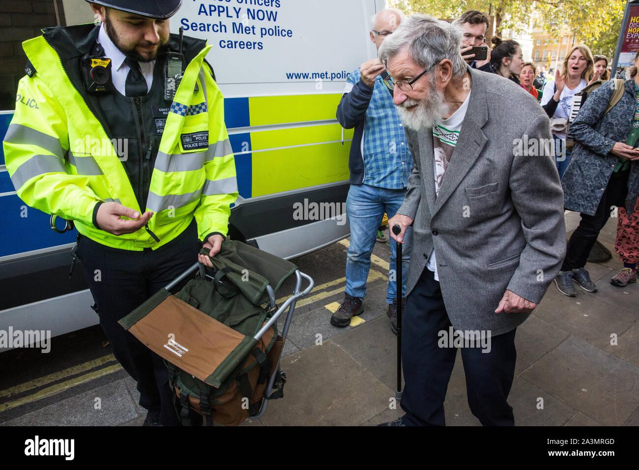 Londres, Royaume-Uni. 9 octobre, 2019. John Lynes, 91 ans, activiste climatique de l'extinction, la rébellion est arrêté par des policiers à l'aide de l'article 14 de la Loi sur l'ordre public de 1986 après le blocage Whitehall le troisième jour de manifestations internationales d'exiger une rébellion Déclaration gouvernementale d'un climat et d'urgence écologique, un engagement à enrayer la perte de biodiversité et la consommation énergétique nette zéro émissions de carbone en 2025 et pour le gouvernement de créer et d'être entraîné par les décisions d'une assemblée de citoyens sur le climat et la justice écologique. Credit: Mark Kerrison/Alamy Live News Banque D'Images