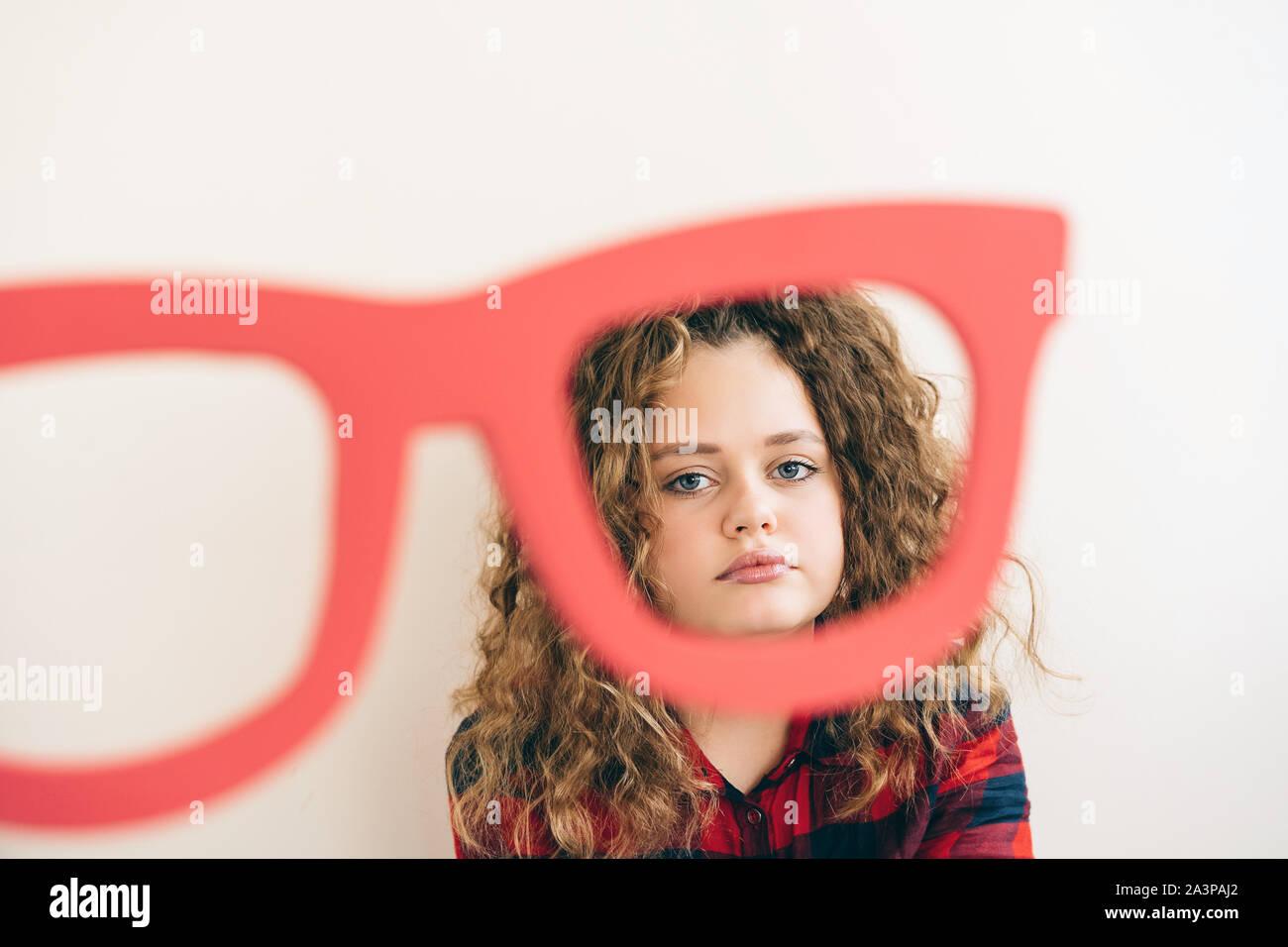 Aux longs cheveux bouclés cute teen blonde girl ressemble plus drôle de grands verres de couleur rouge Banque D'Images