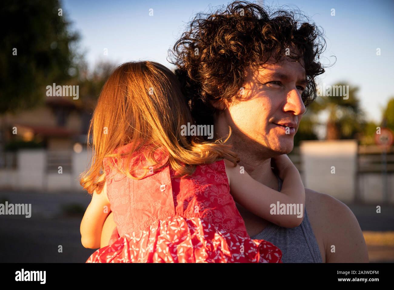 Jeune père tenant sa petite fille piscine au coucher du soleil. L'homme est à la recherche, tandis que l'enfant est vue de dos portant une robe rouge. Banque D'Images