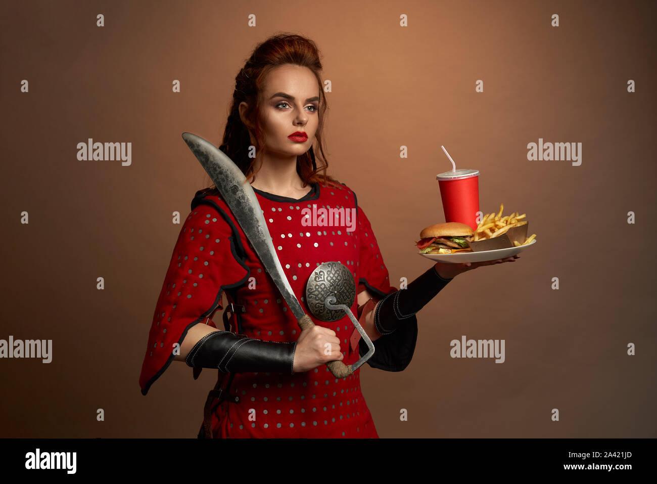 Belle femme fighter en armure rouge garder grand couteau et la plaque avec la restauration rapide en studio. Femme déterminée à côté et posant avec un hamburger et une pomme de terre. Concept de l'alimentation des héros. Banque D'Images