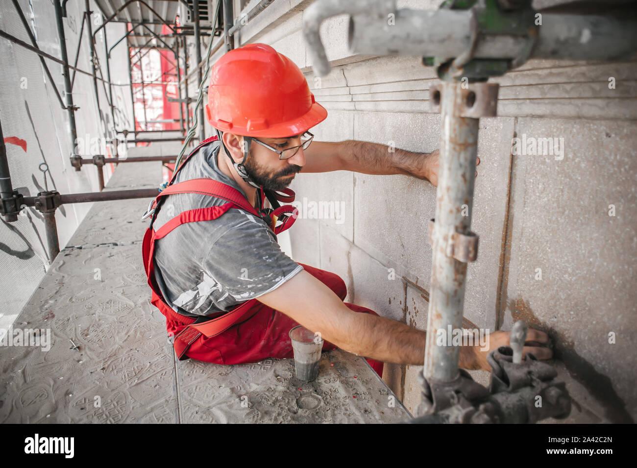 Travailleur de la construction mason sur l'échafaudage de mélanger du ciment et du sable à l'aide d'une spatule sur le site de construction Banque D'Images