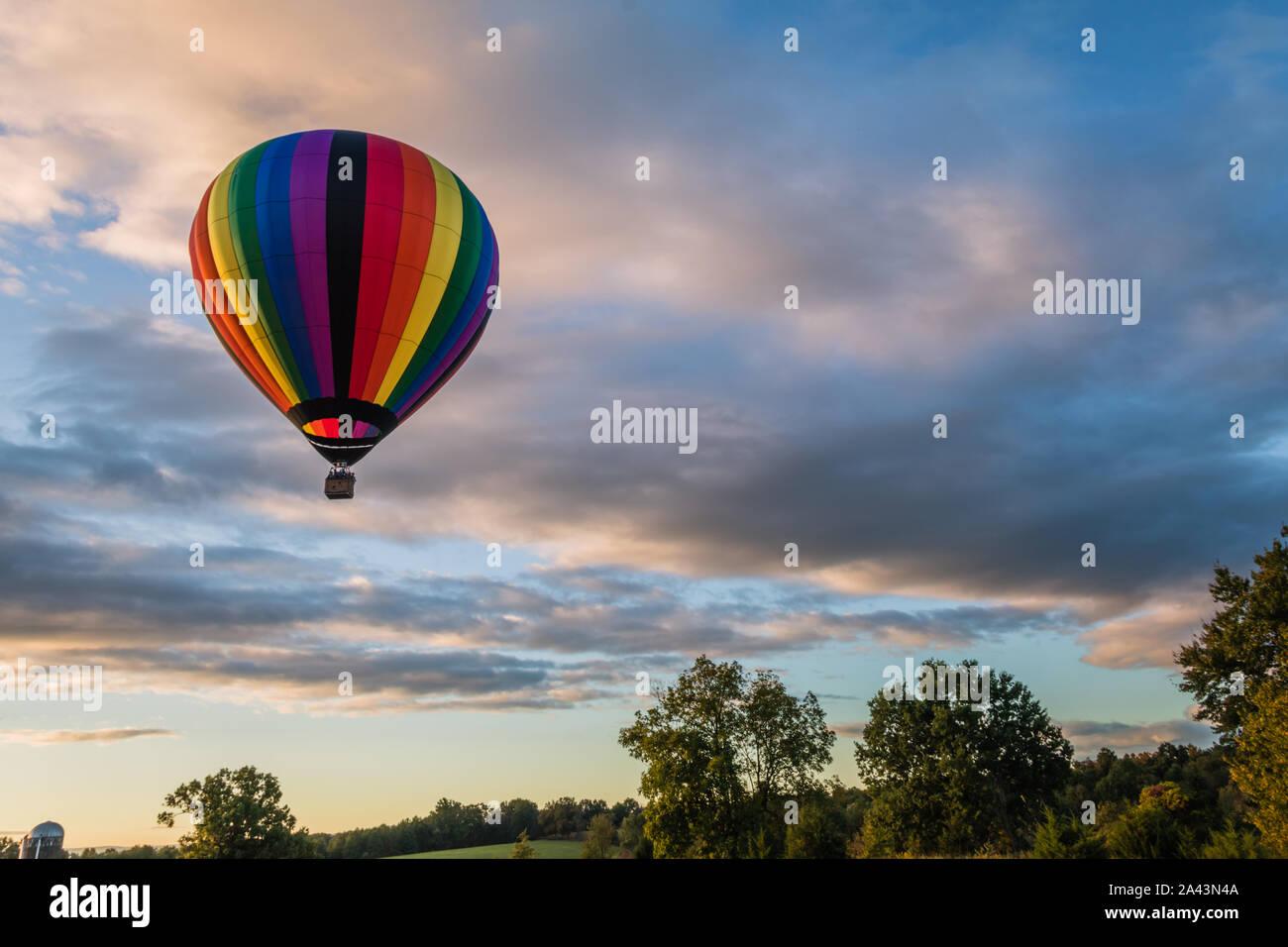 Montgolfière arc-en-ciel flotte au-dessus au lever du soleil sur le terrain Banque D'Images