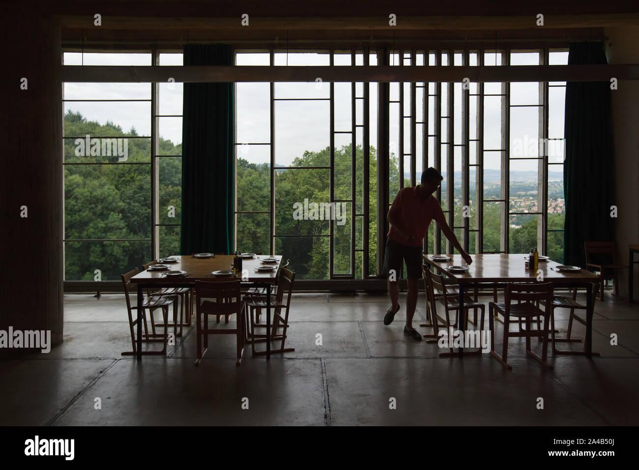 L'homme sert de la table dans le réfectoire monastique dans le Monastère de Sainte Marie de La Tourette conçu par l'architecte suisse Le Corbusier (1959) de Éveux près de Lyon, France. Banque D'Images
