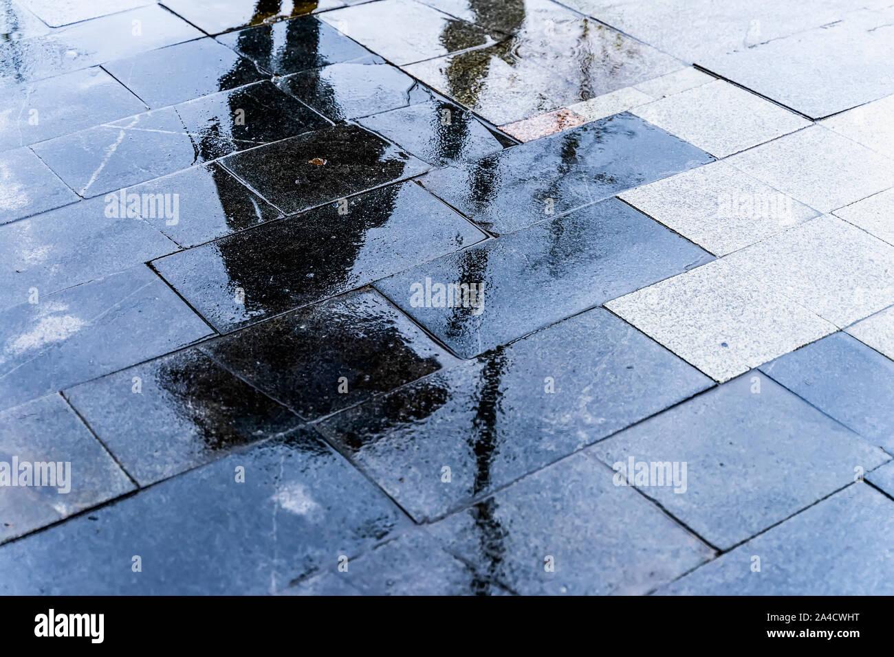 Réflexion floue ombre silhouette d'une femme de marcher sous parapluie dans une ville piétonne Rue humide dans une flaque, soir de pluie d'automne Banque D'Images