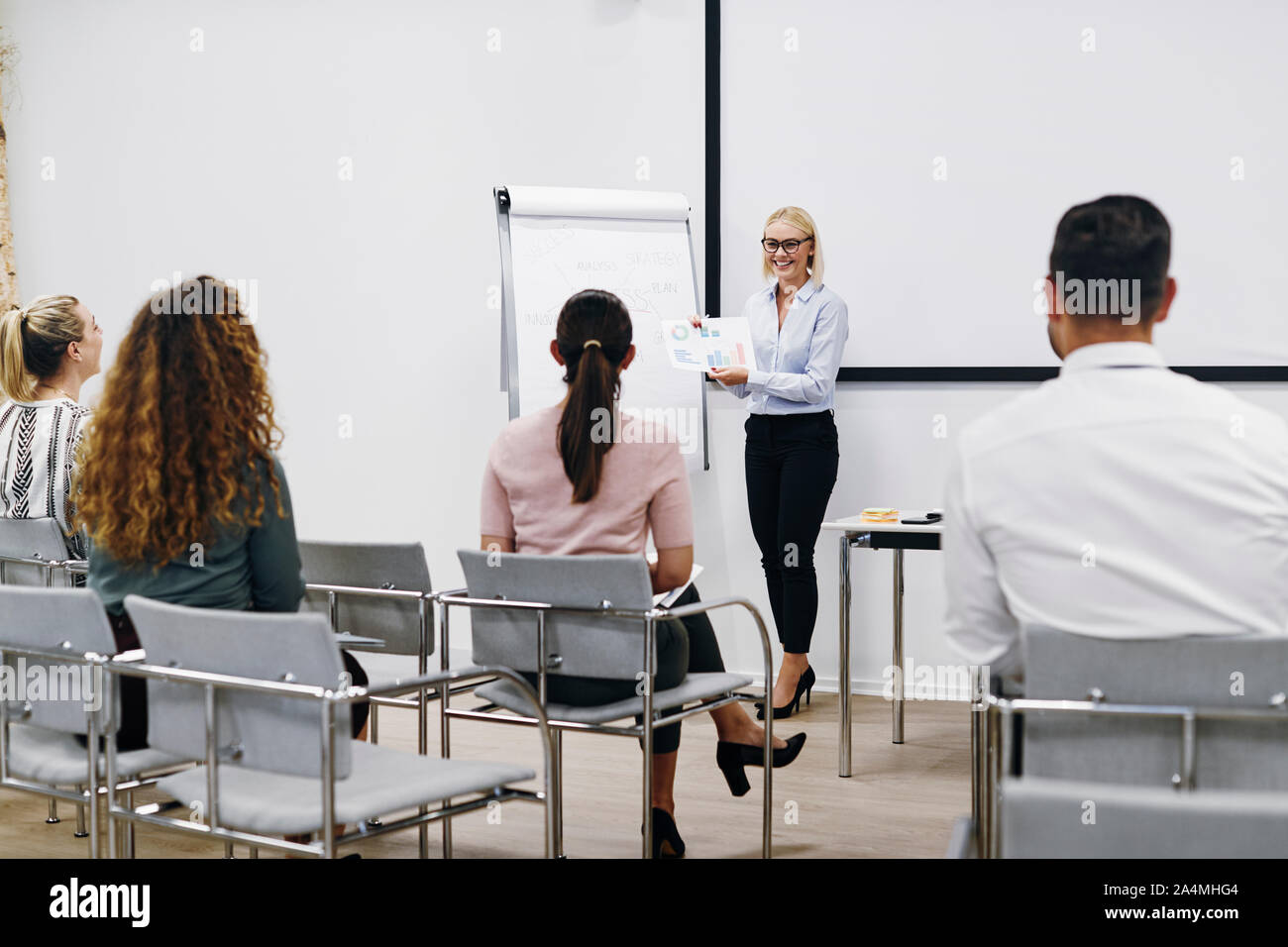 Smiling manager passe plus de graphiques et tableaux au cours d'une présentation au personnel dans une salle de réunion dans un bureau Banque D'Images