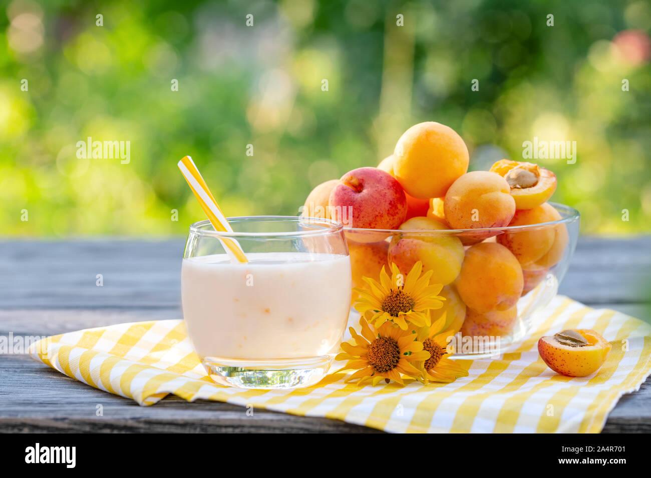 Smoothie à l'abricot ou du yaourt aux abricots sur table en bois. Fond naturel vert Banque D'Images