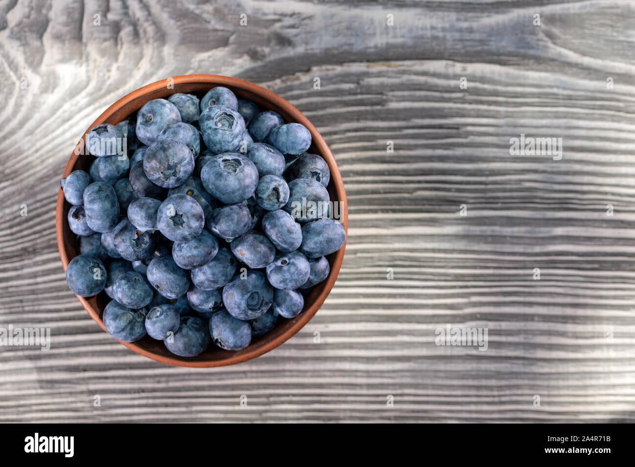 Bleuets dans un bol d'argile sur une table en bois. Vue de dessus. Toujours été la vie. Produit naturel et concept de récolte Banque D'Images