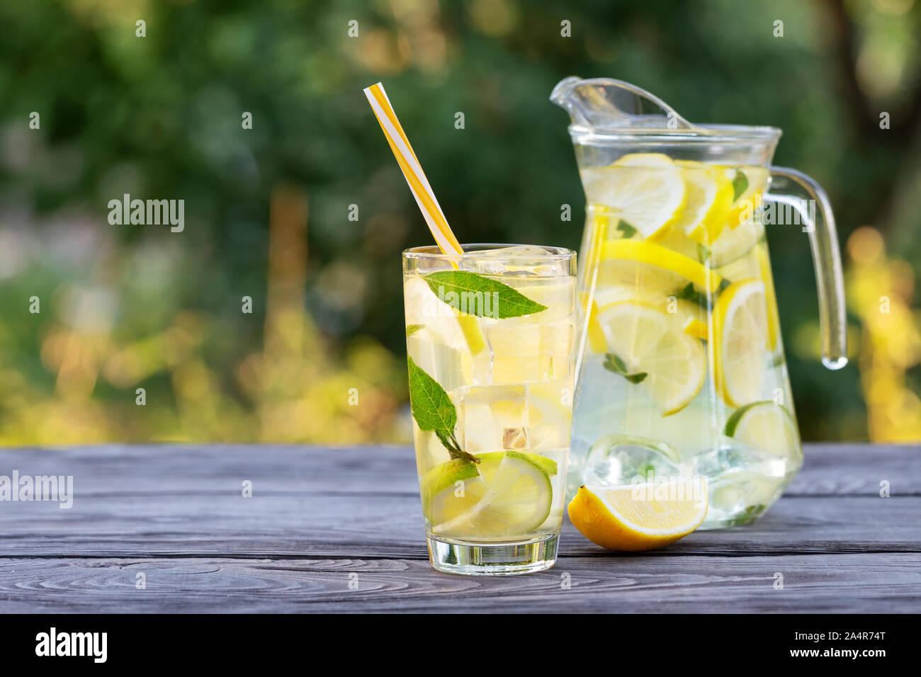 Verseuse en verre et de limonade et tranche de citron sur la table en bois. Fond vert naturel. Rafraîchissement d'été Banque D'Images