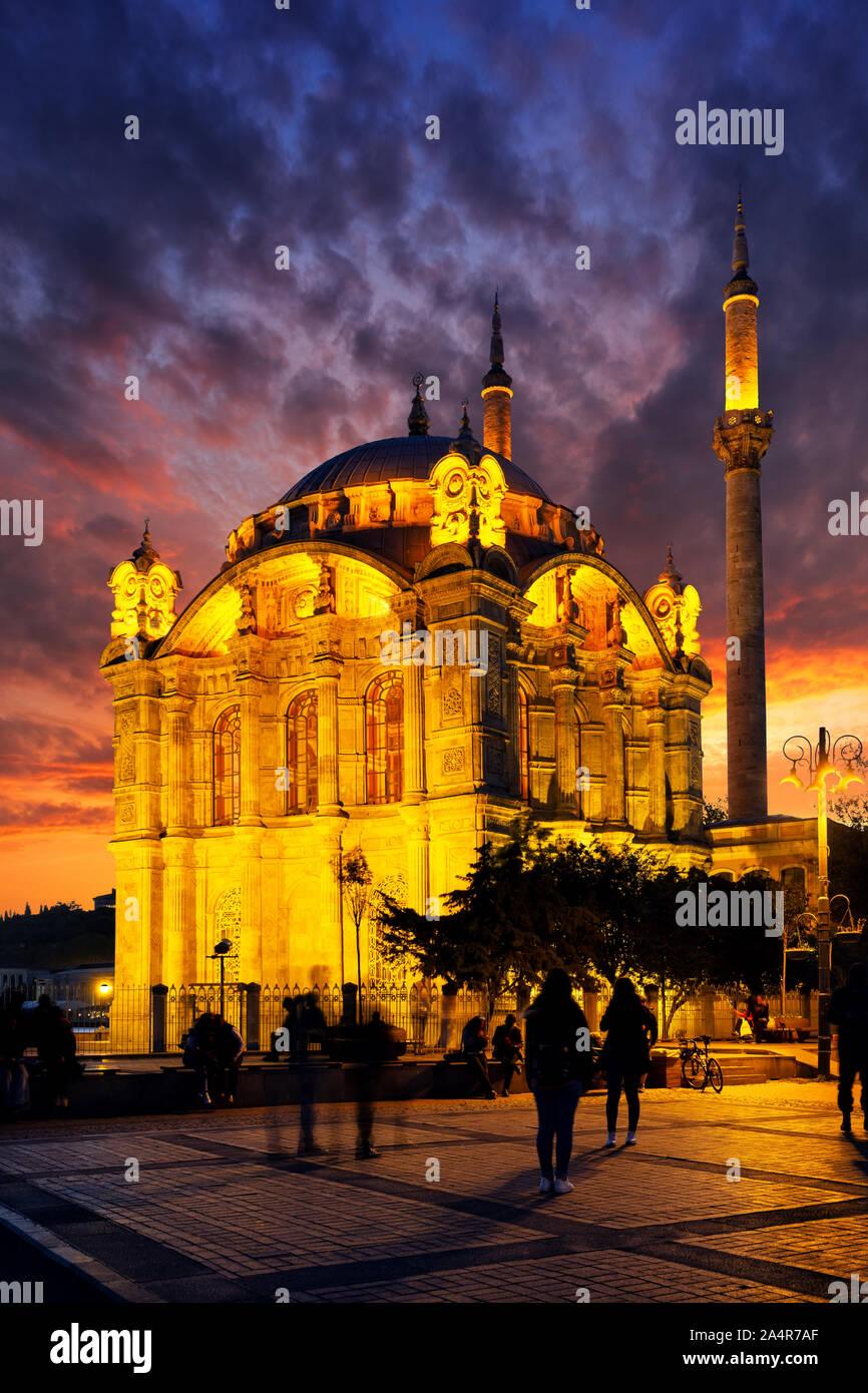 Mosquée Ortakôy à Istanbul au coucher du soleil. Ciel dramatique. L'une des principales attractions d'Istanbul. Silhouettes de personnes, les visages ne sont pas reconnaissables. La Turquie Banque D'Images