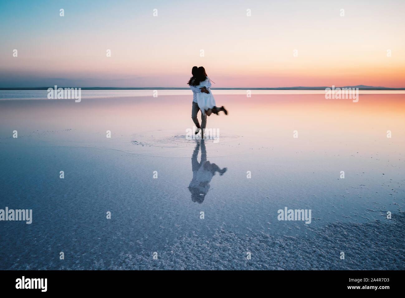 Silhouettes d'étreindre les amoureux heureux au milieu de l'eau peu profonde d'un lac au coucher du soleil. Le concept de l'amour, le bonheur, la famille, la solitude. Banque D'Images