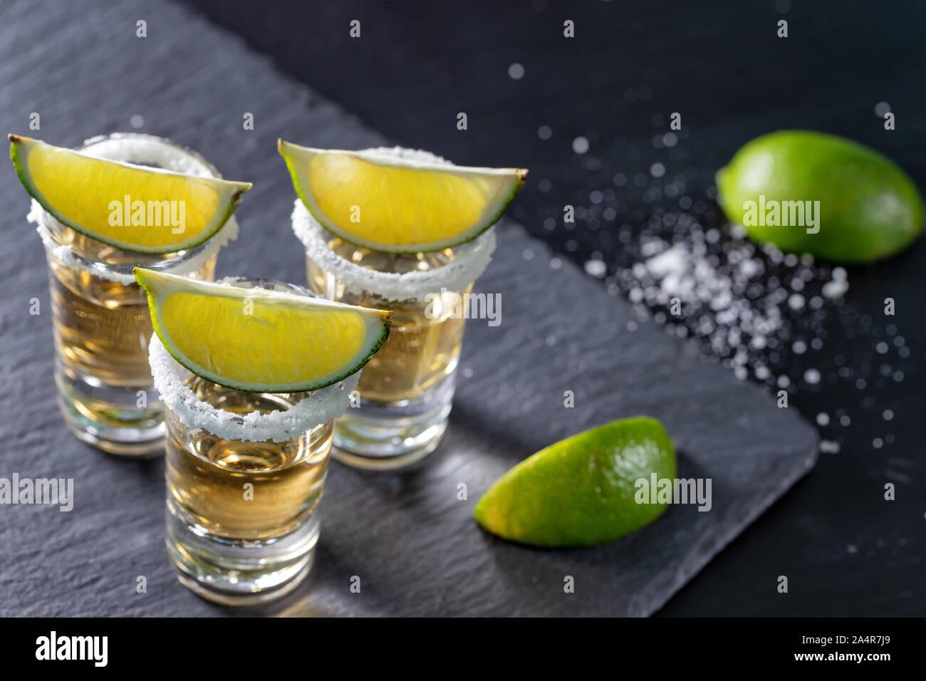 Trois verres de tequila mexicaine et de la chaux sur fond sombre Banque D'Images