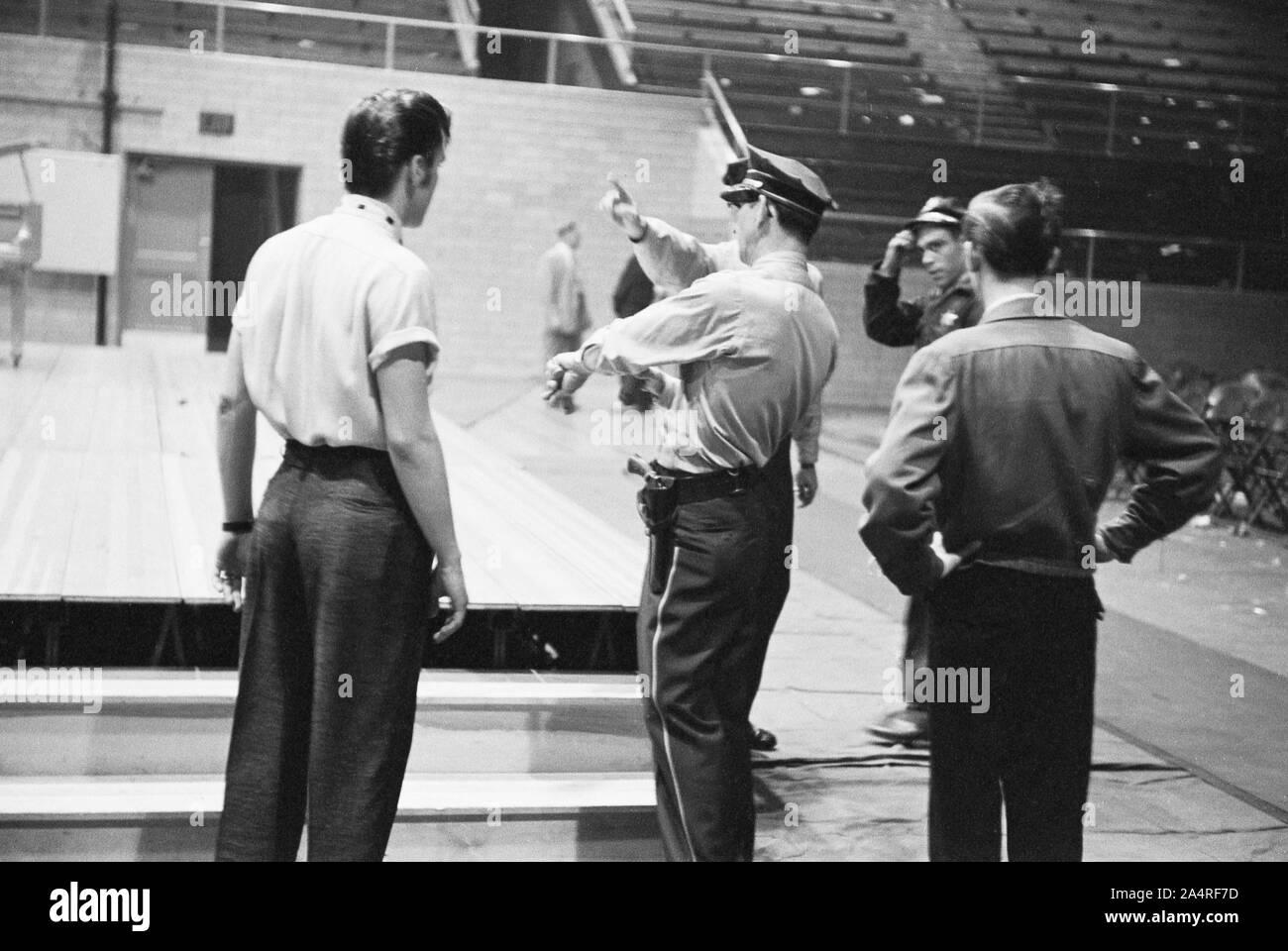 Elvis Presley parle avec les fonctionnaires de police à l'Université de Dayton Fieldhouse, le 27 mai 1956. Banque D'Images