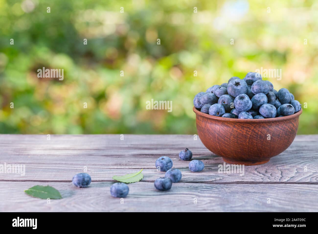 Bleuets dans un bol d'argile sur une table en bois Banque D'Images