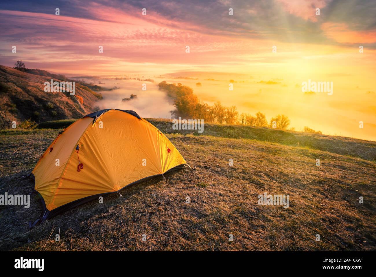 Tente d'Orange sur la colline au-dessus de la rivière de brouillard sous un soleil éclatant Banque D'Images