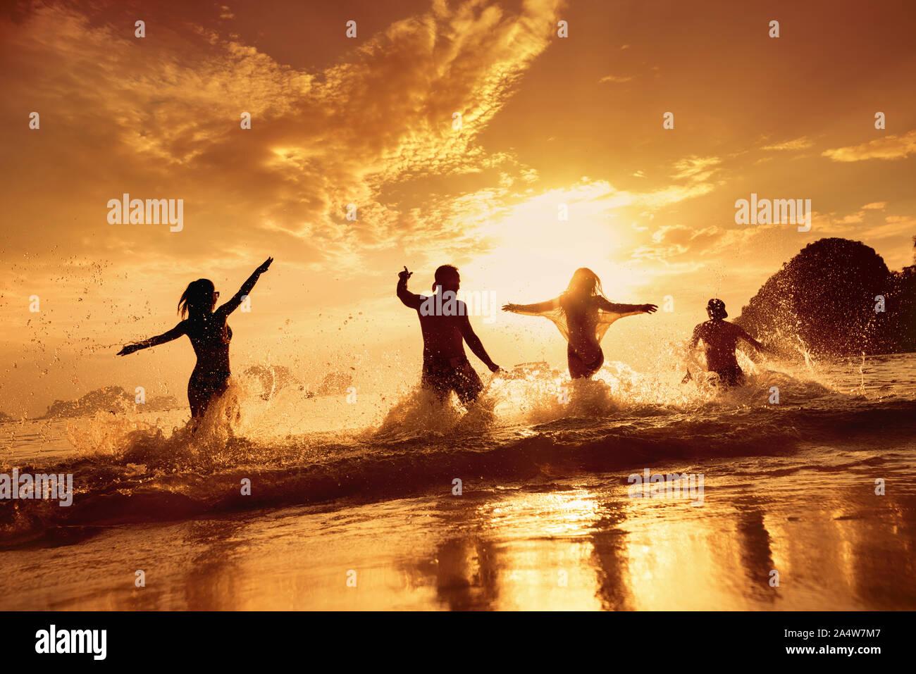 Quatre amis heureux s'exécute et s'amusant à beau coucher de soleil mer plage Banque D'Images