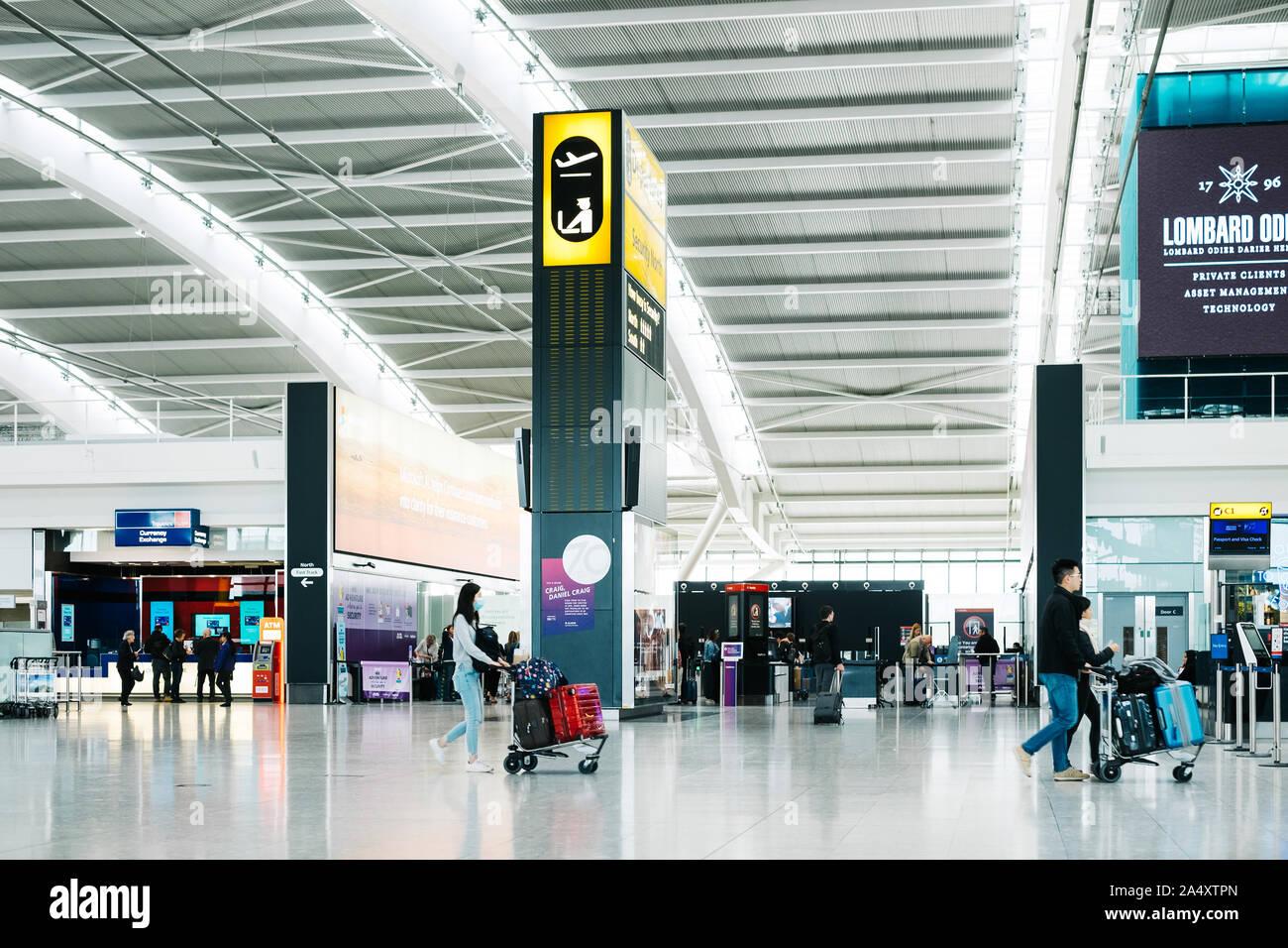 Les passagers à pied à l'intérieur de l'aéroport international de Londres Heathrow Terminal 5 hall des départs. Femme Asiatique porte un masque et pousse avec une assurance dans le panier. Banque D'Images