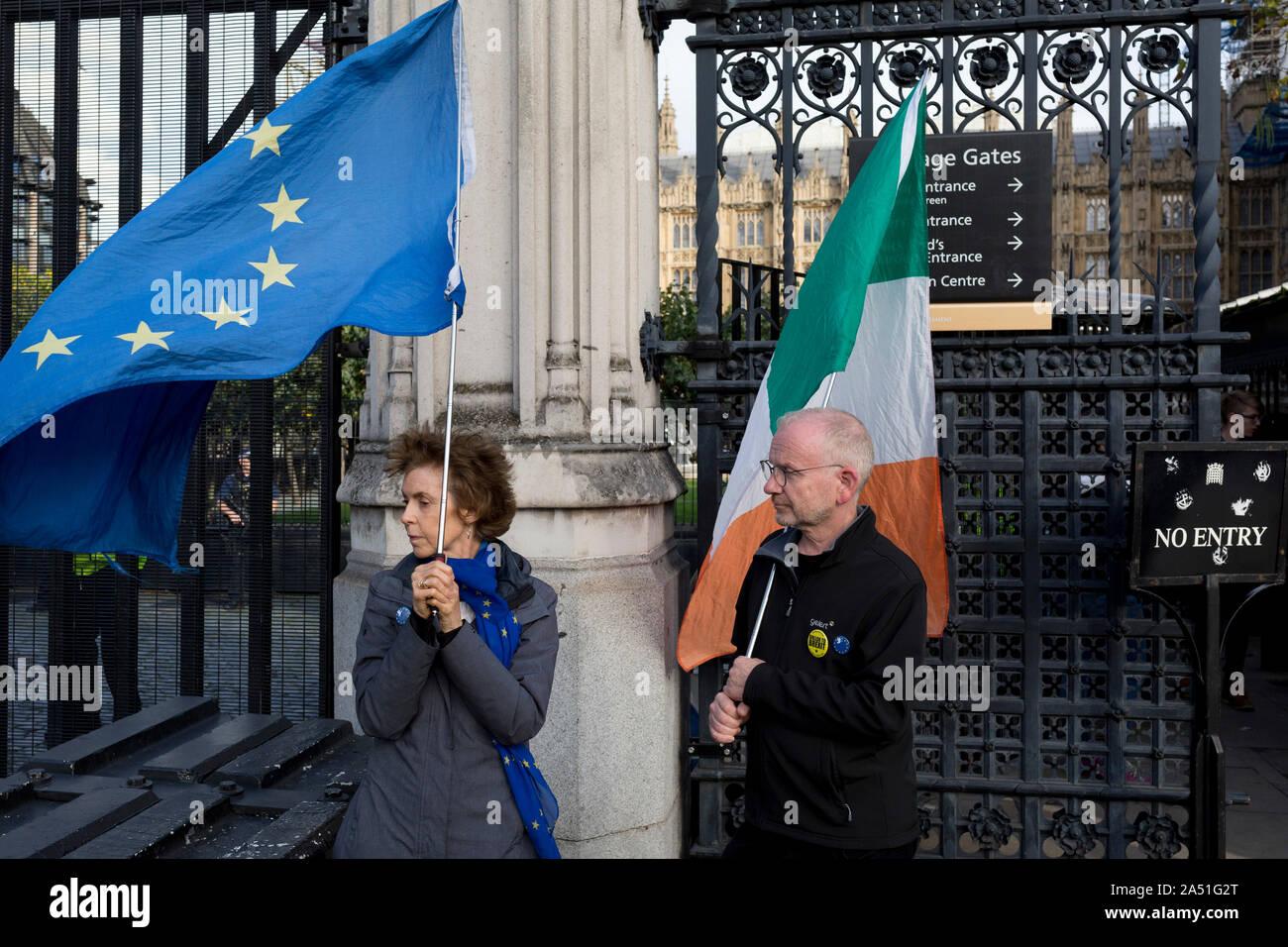 Le jour où le premier ministre Boris Johnson négocie avec Bruxelles sur un Brexit traiter, et lorsque le Parti unioniste démocratique (DUP) rejeter ses propositions, pro-Union européenne Brexit manifestants tenant la République irlandaise de l'UE et se positionner sous les drapeaux du Parlement britannique garde-fous aux transport porte sur la place du Parlement, le 16 octobre 2019, à Westminster, Londres, Angleterre. Banque D'Images