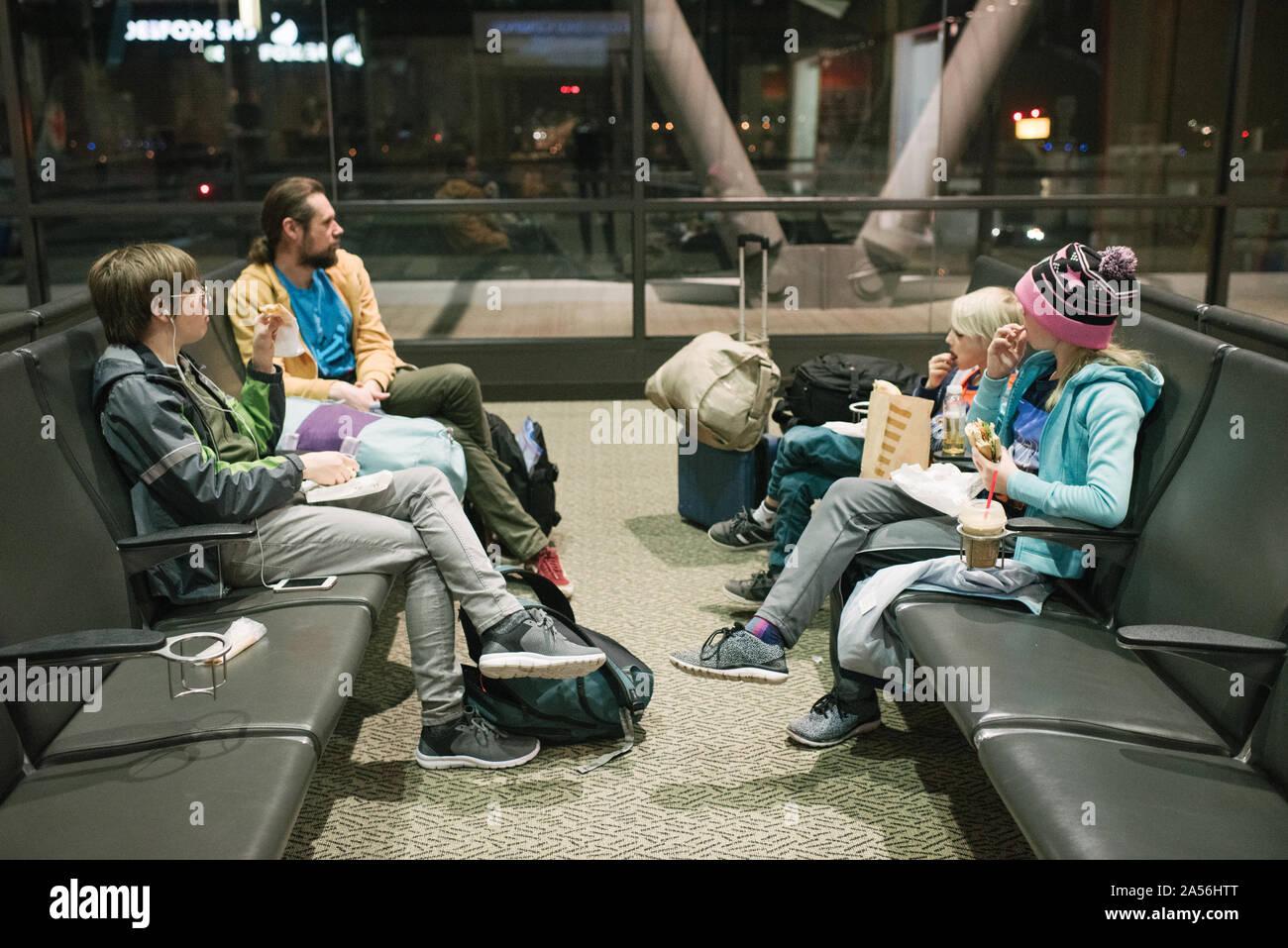 Homme mature avec fils et fille en attente dans la salle d'embarquement de l'aéroport de manger des collations Banque D'Images