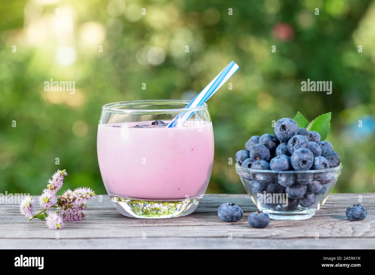 Yogourt frappé aux bleuets ou dans du verre tasse avec de la paille et de baies. Table en bois. Le concept de santé et de désintoxication natural nutrition Banque D'Images