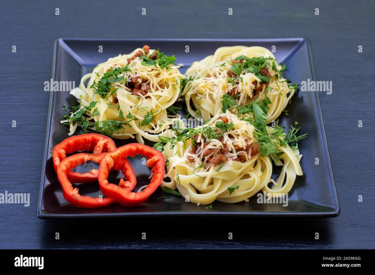 Spaghetti à la viande fromage râpé et poivron rouge sur une plaque noire. Fond noir. Plat italien traditionnel Banque D'Images