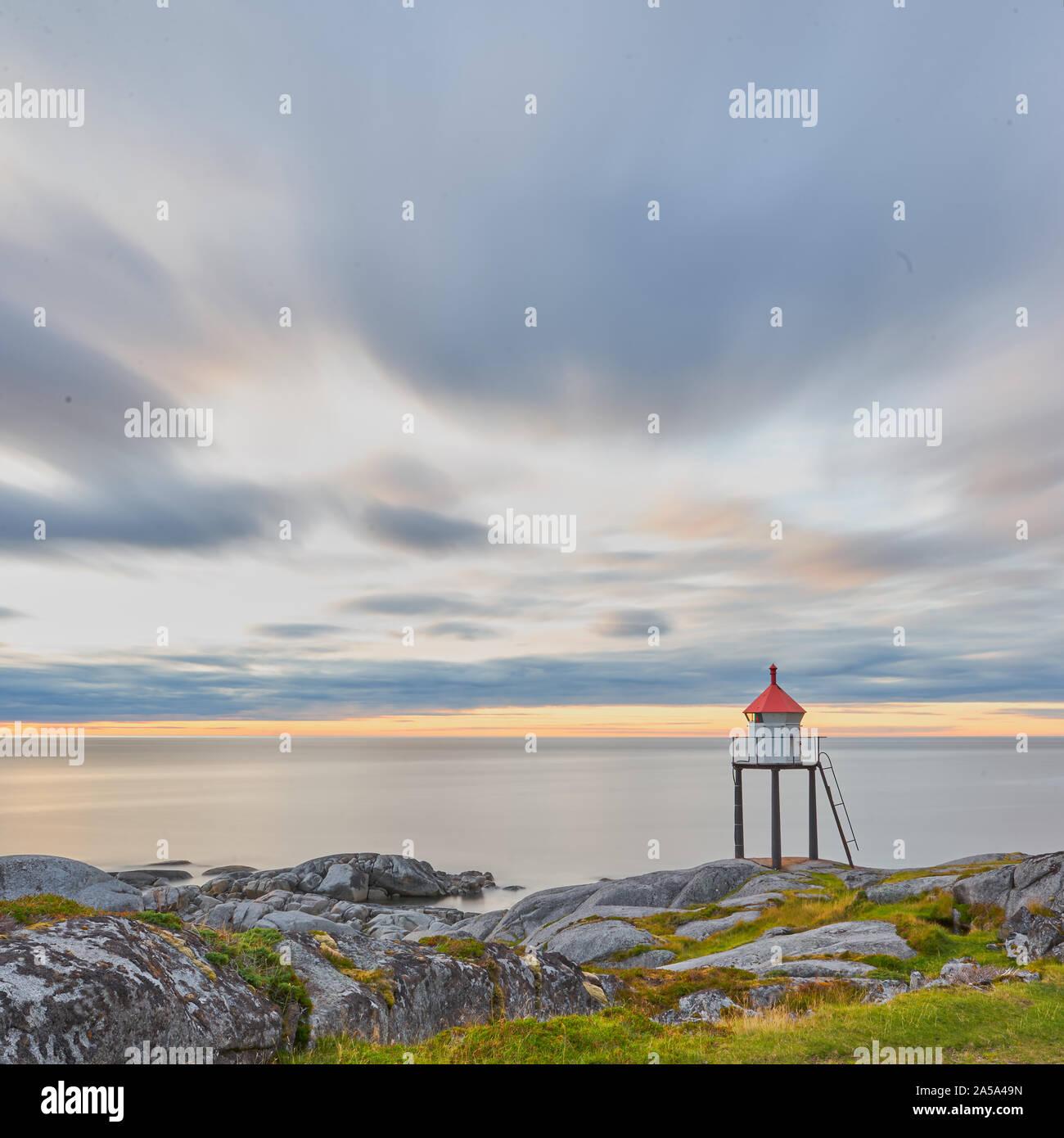Une chaude lumière peut être vu dans le ciel. Le phare se dresse au premier plan sur la côte. Un beau moment. Banque D'Images