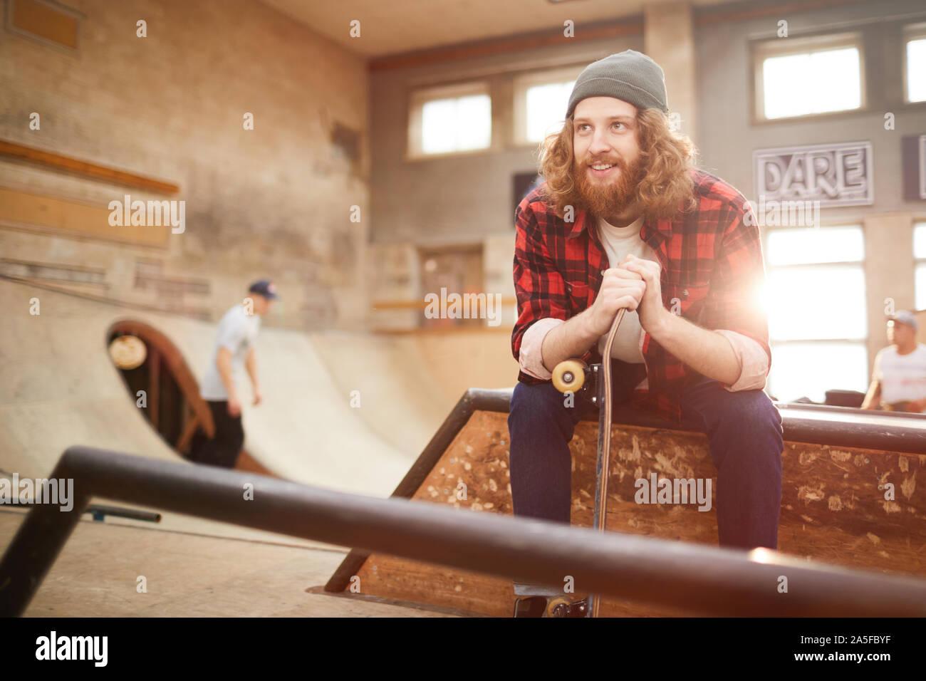 Portrait d'homme barbu contemporain à l'écart et souriant assis sur la rampe en skating park, copy space Banque D'Images