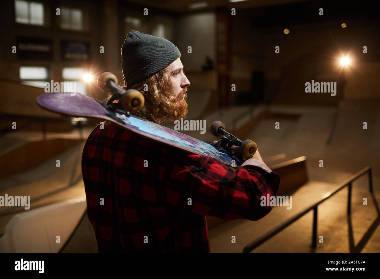 Vue arrière de la patineuse barbu à l'air songeur, tout en se posant en milieu urbain parc patinage éclairé par de faibles lumières, copy space Banque D'Images