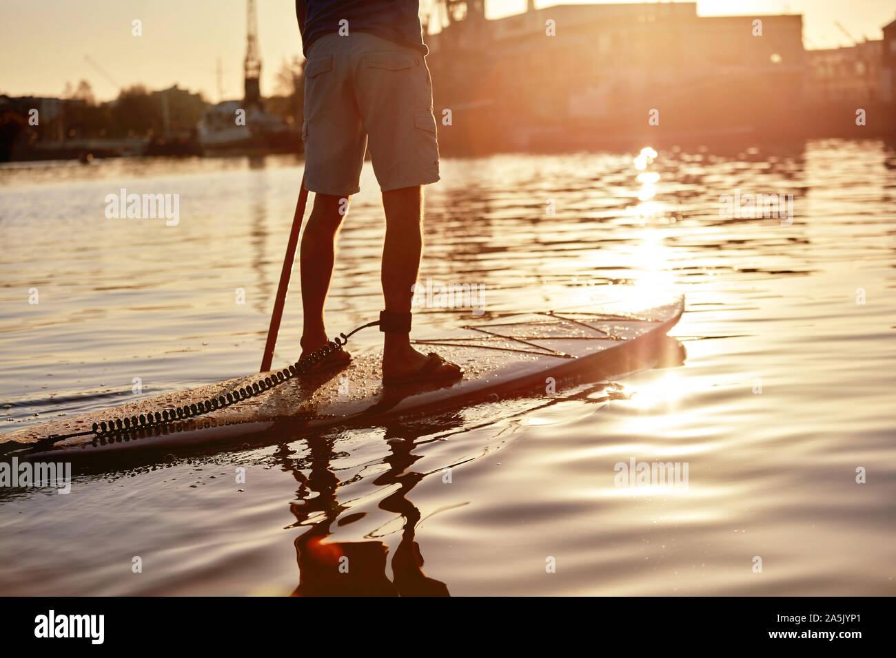 Homme debout sur le paddleboard sur rivière à l'aube, tourné par derrière Banque D'Images
