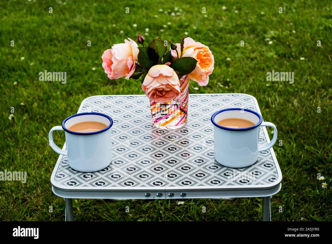 High angle close up de thé dans des tasses en émail blanc et vase avec des roses rose saumon sur table de pique-nique. Banque D'Images