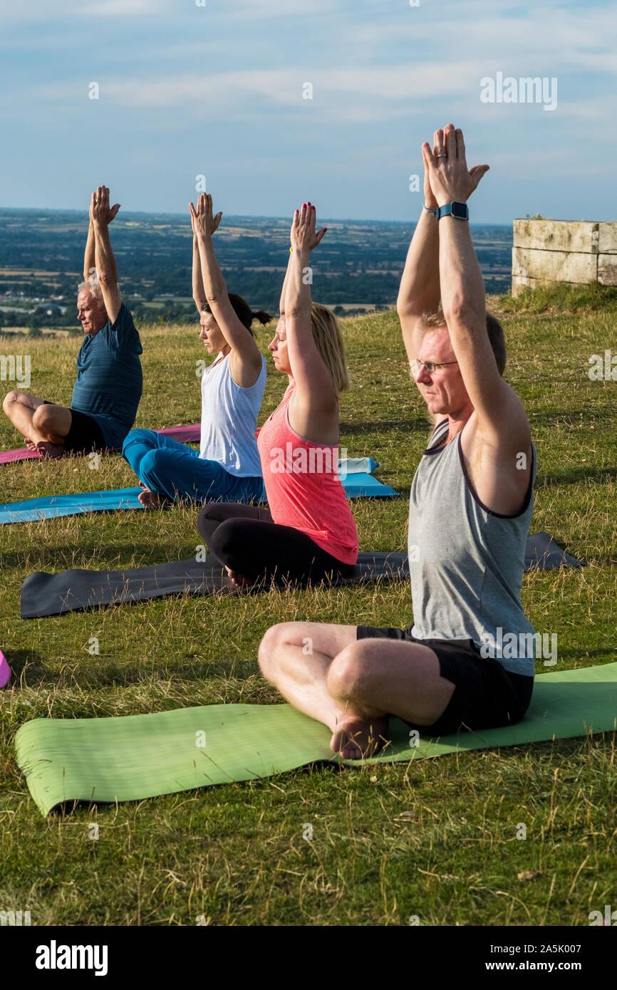 Groupe de femmes et d'hommes participant à une classe de yoga sur une colline. Banque D'Images