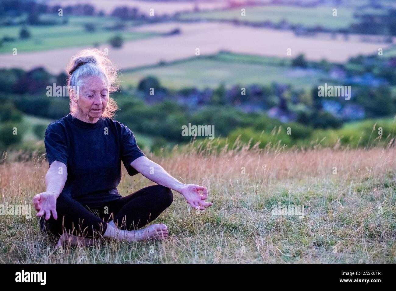 Hauts femme participant à une classe de yoga sur une colline. Banque D'Images