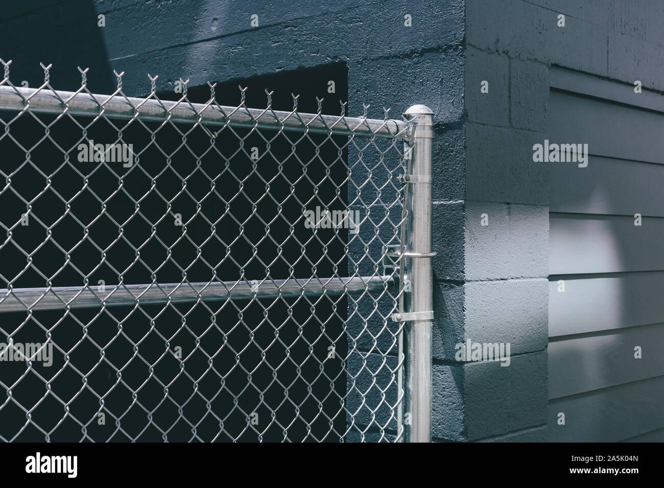 Chaîne lien grillage sur la porte du bâtiment, les graffitis de pulvérisation de peinture sur mur urbain Banque D'Images