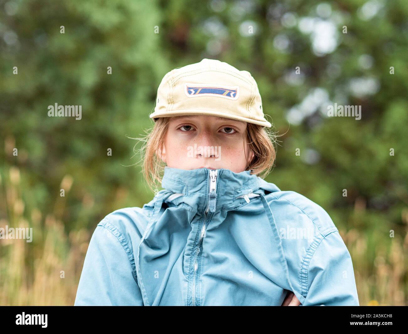 Portrait of teenage boy with wind breaker et hat outdoors Banque D'Images