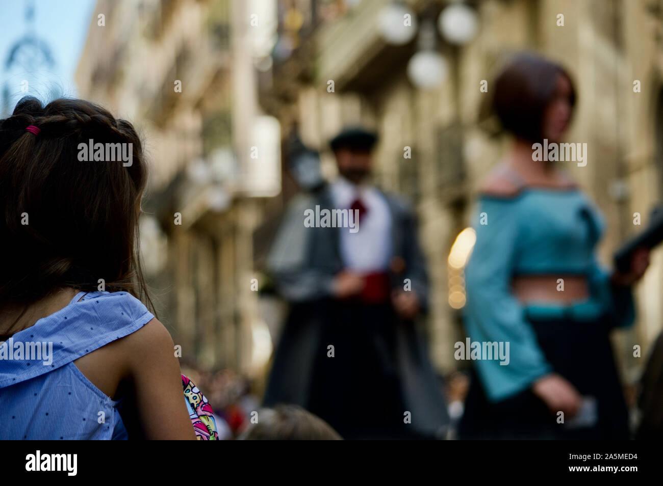 Une jeune fille regarder la parade de géants au cours de la Merce 2019 Festival à Plaça de Sant Jaume de Barcelone, Espagne Banque D'Images