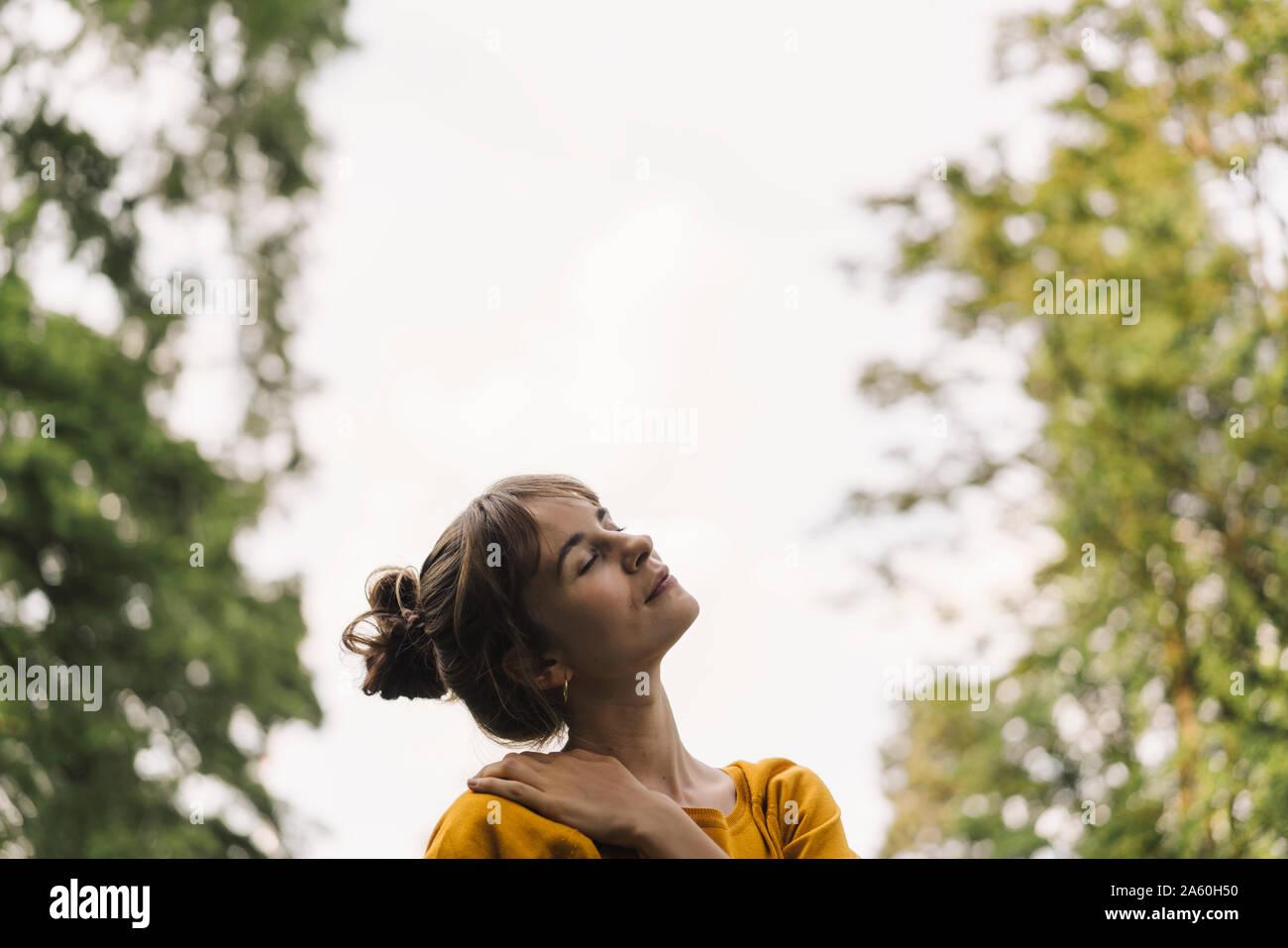 Jeune femme détendue dans un parc Banque D'Images