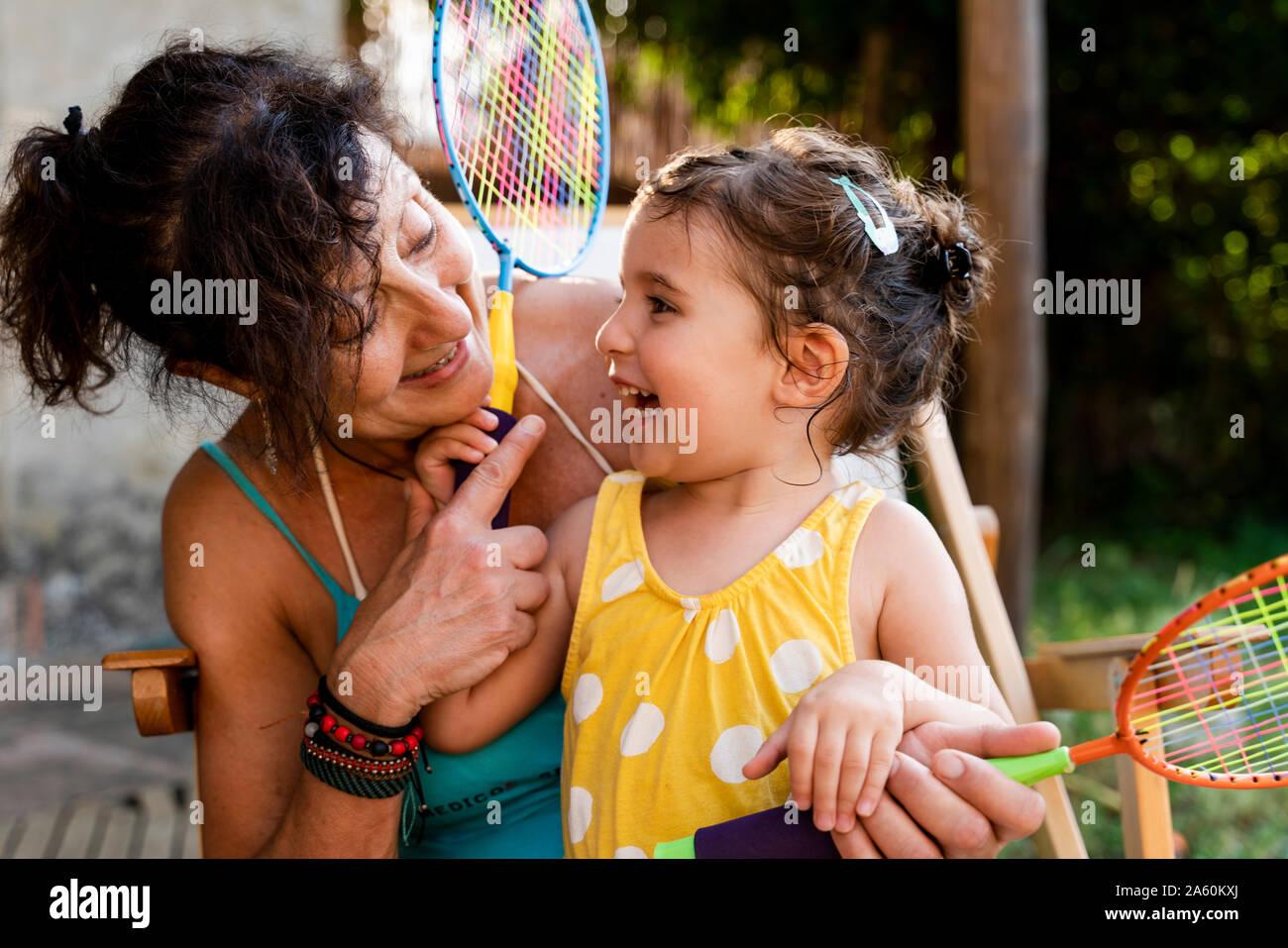 Grand-mère jouant avec petite fille et raquettes de badminton en plein air Banque D'Images