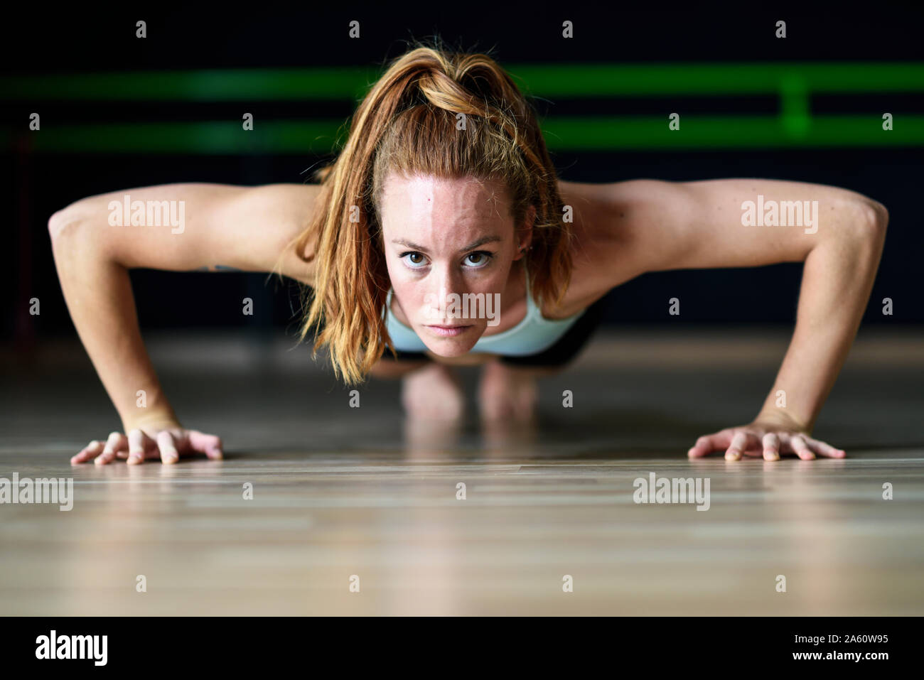 Sporty young woman doing push-ups dans une salle d'exercice Banque D'Images
