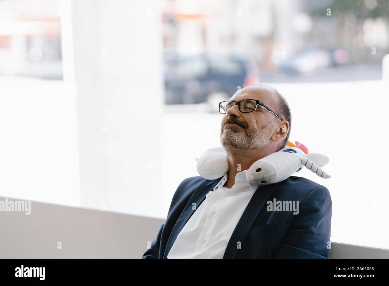 Businessman prendre une sieste, avec un oreiller unicorn autour du cou Banque D'Images