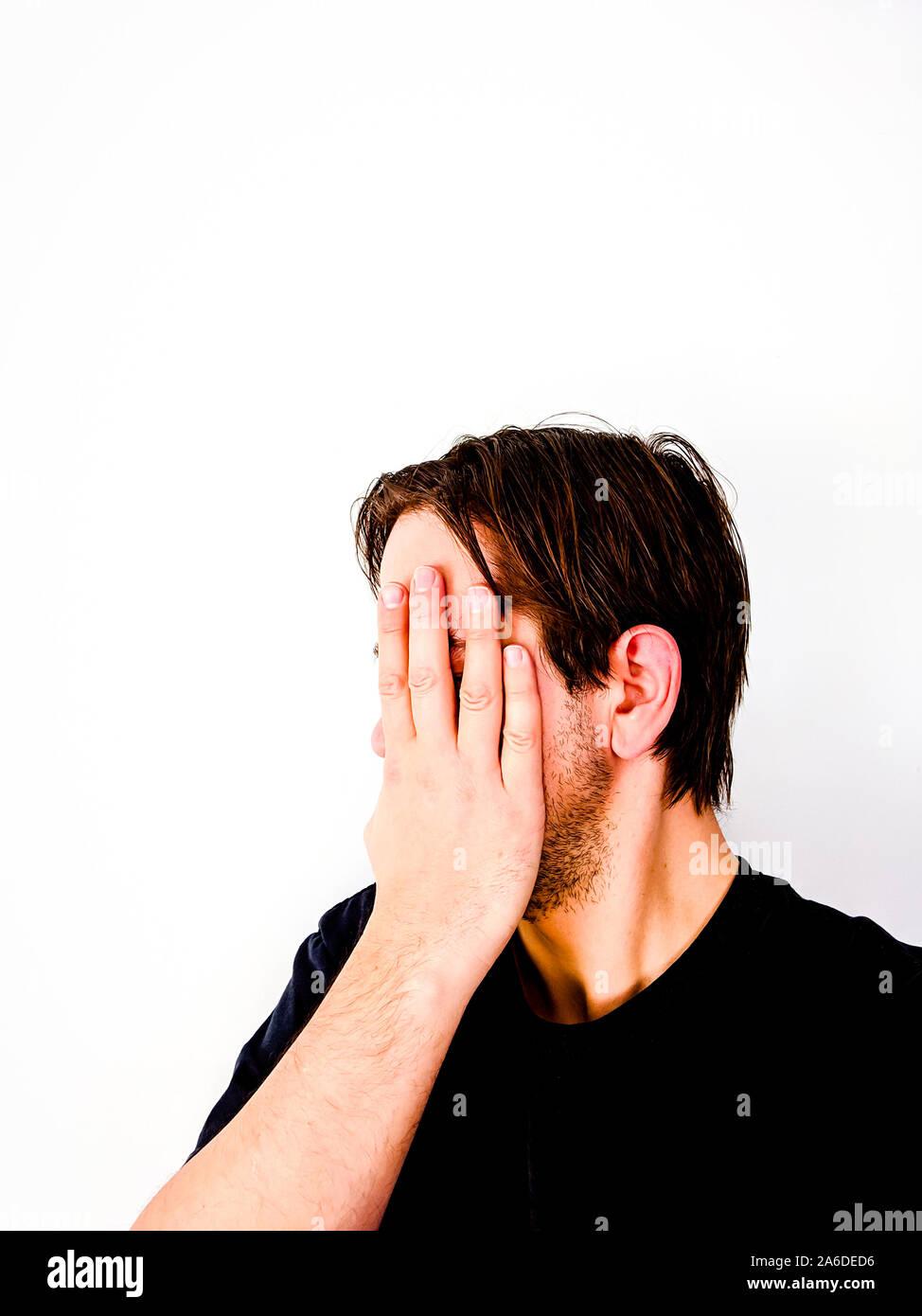 L'homme qui couvre le visage avec la main dans la honte - vue latérale Banque D'Images
